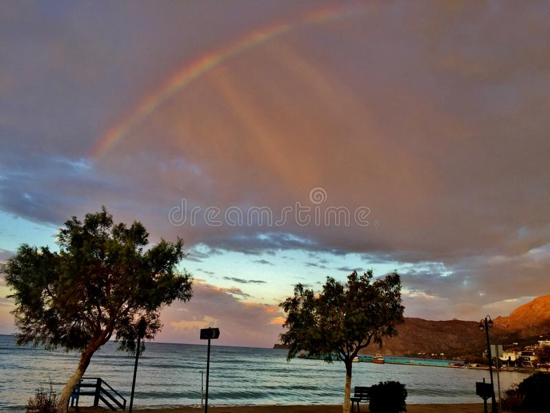 Mooie mening van het overzees na regen met een regenboog in de hemel stock afbeelding