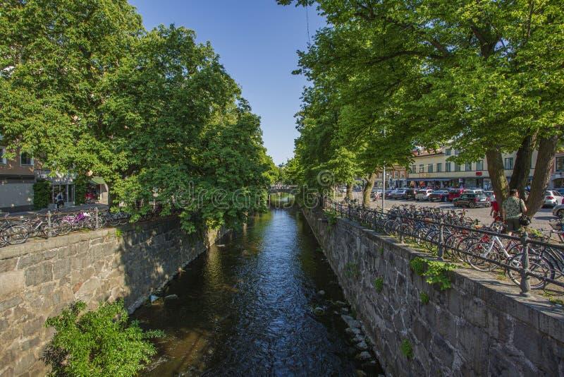 Mooie mening van stadsstraat met de spelen van het fietsparkeren op rivier zij en oude groene bomen Mooie aardachtergronden stock afbeelding
