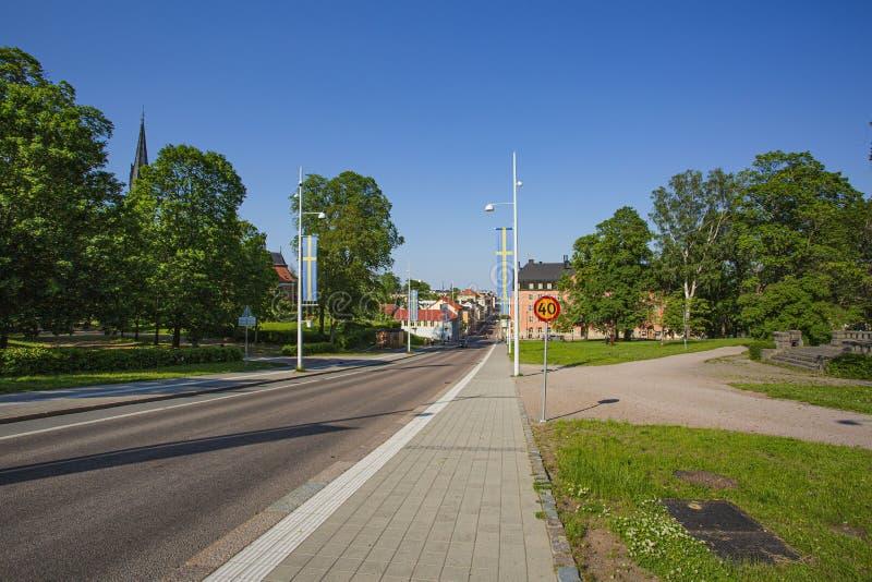 Mooie mening van stadsweg met Zweedse vlaggen tijdens Zweedse nationale dag Groene bomen en blauwe hemelachtergrond royalty-vrije stock foto