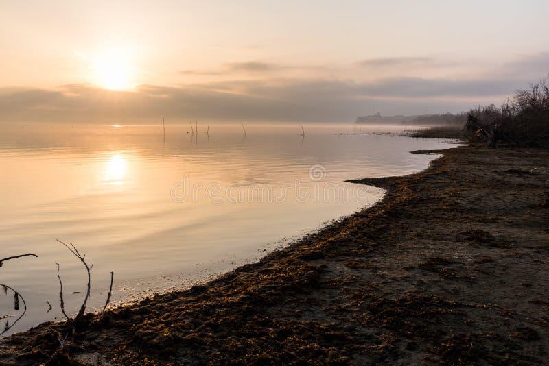 Mooie mening van Trasimeno-de kust van meerumbrië bij dageraad, met Castiglione del Lago stad bij de afstand royalty-vrije stock foto's
