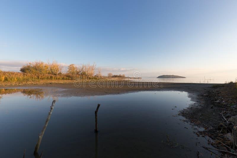 Mooie mening van Trasimeno-meerkust Umbrië, Italië, met totaal lege blauwe hemel die water overdenken royalty-vrije stock afbeelding