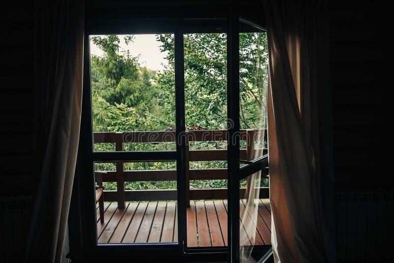 Mooie mening van venster op portiek op bomen in hout plattelandshuisje B stock afbeelding