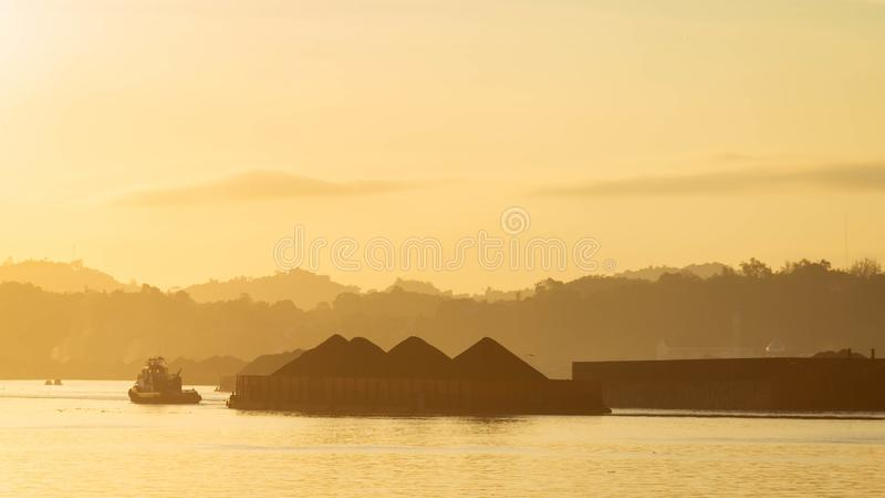 Mooie mening van verkeer van sleepboten die aak van steenkool trekken bij Mahakam-Rivier, Samarinda, Indonesië bij dageraad royalty-vrije stock foto