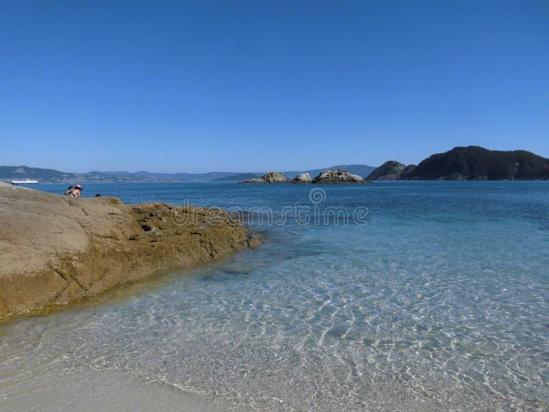 Mooie mening van wit zandstrand en blauw en kristallijn water met duidelijke hemel op het strand Rhodes Cies Islands stock foto