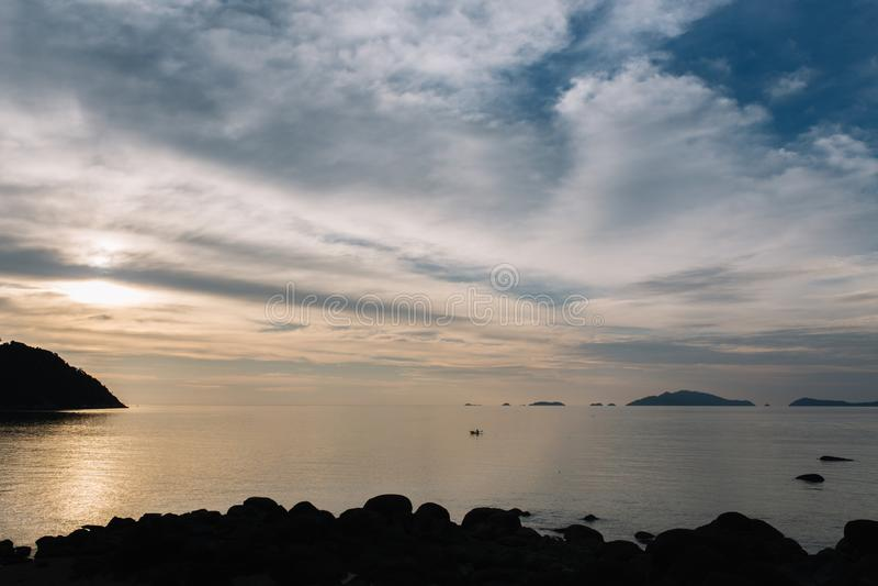 Mooie mening van zonsondergang bij strand met mensen het kayaking stock afbeeldingen