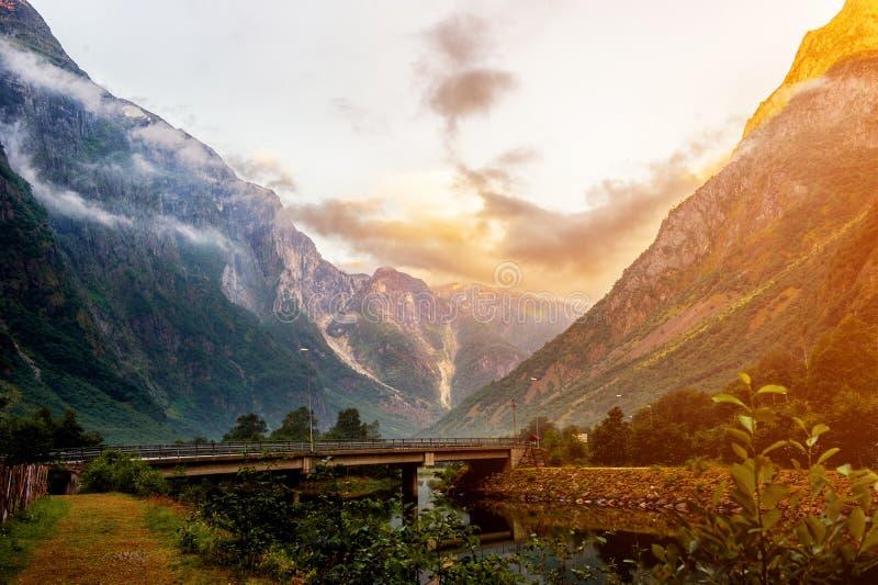 Mooie meningen van de zonsopgang over de fjord en de bergen van de brug in het Noorse dorp van Gudvangen royalty-vrije stock foto's