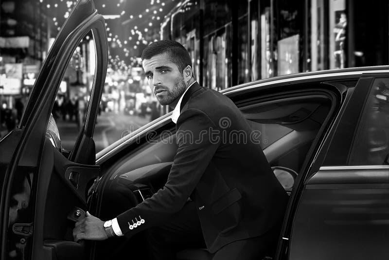 Mooie mens dichtbij de auto, zwart-wit foto royalty-vrije stock afbeelding
