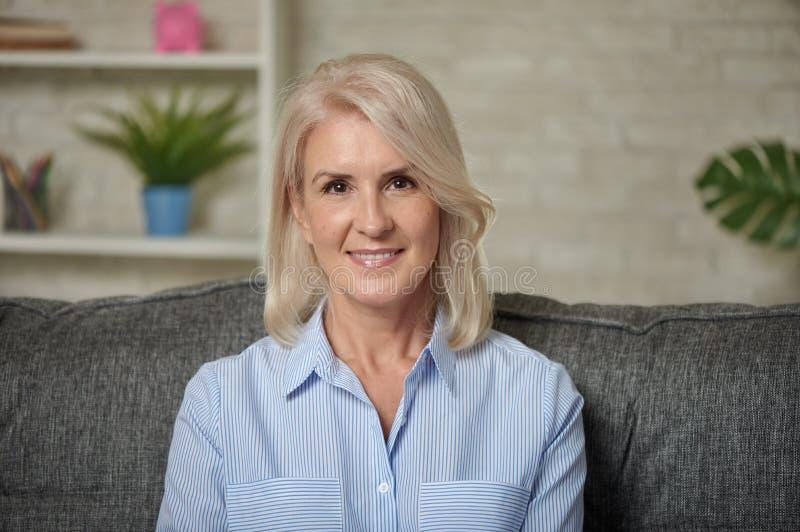 Mooie midden oude blonde vrouw met een richtende glimlach stock foto