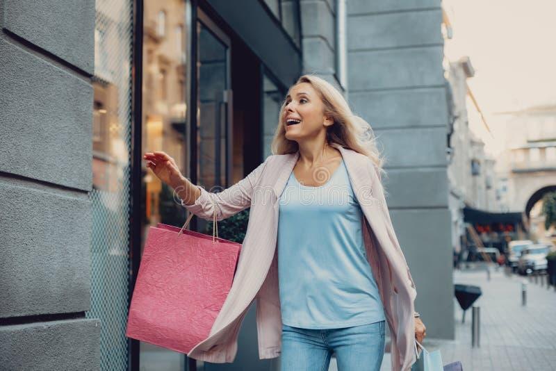 Mooie midden oude vrouw die kleren in de opslag haasten zich te kopen stock foto's