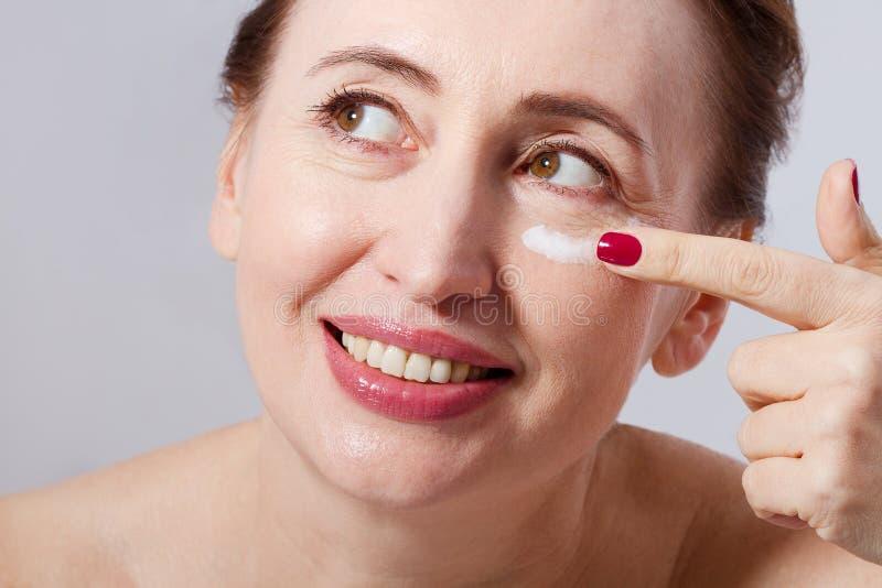 Mooie midden oude vrouw die kosmetische roombehandeling op gezicht op grijze achtergrond toepassen Spot omhoog en exemplaarruimte royalty-vrije stock foto's
