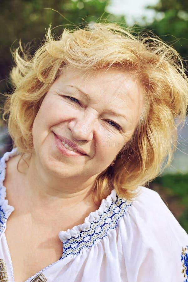 Mooie midden oude vrouw die met glimlach de camera bekijken royalty-vrije stock fotografie