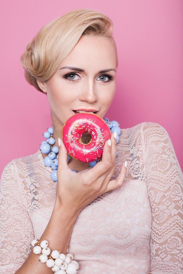 Mooie midden oude vrouwen die kleurrijke doughnut proeven Zachte kleuren royalty-vrije stock afbeeldingen