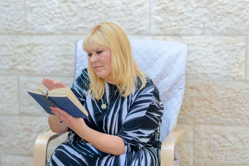 Mooie middenleeftijds Skandinavische vrouw in openlucht het boekzitting van de terraslezing in leunstoel stock foto's