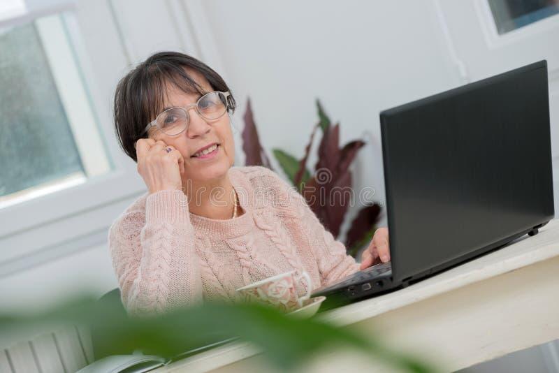 Mooie middenleeftijdsvrouw die laptop in huis met behulp van royalty-vrije stock foto's