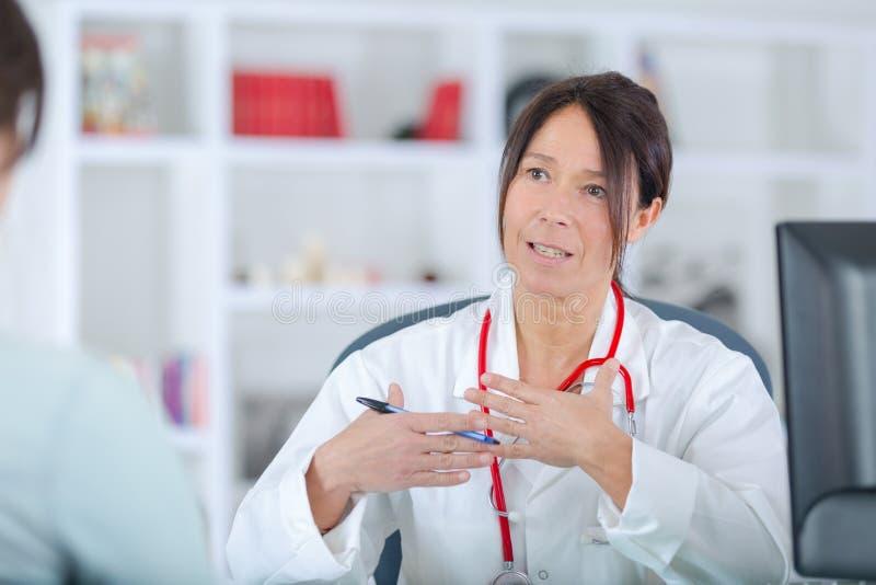 Mooie midle verouderde arts die aan patiënt spreken royalty-vrije stock fotografie