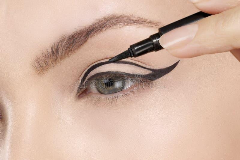 Mooie model het van toepassing zijn eyelinerclose-up op oog stock afbeelding