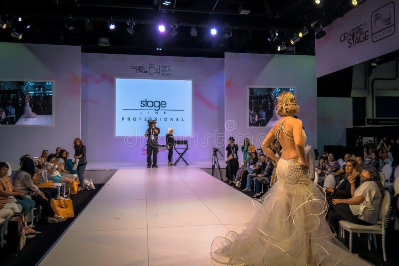Mooie model stellende loopbrug op stadium die huwelijk en bruids kleding tonen royalty-vrije stock foto's