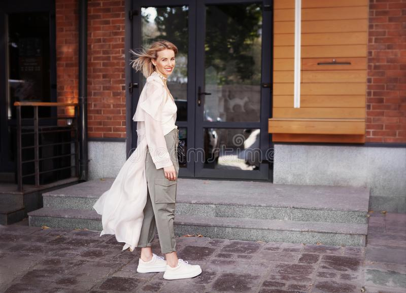 Mooie modemodel glimlachen op City Street Stylish Woman Wearing Fashionable Spring or Autumn Clothes beige trench coat, stock afbeelding