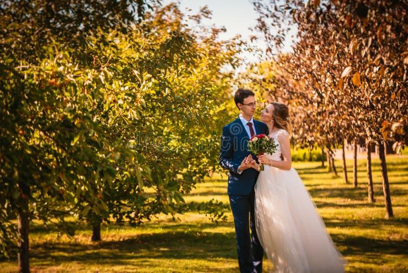 Mooie modieuze bruid en bruidegom op tuinachtergrond stock foto