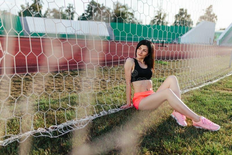 Mooie modieuze donkerbruine vrouw die in zwarte hoogste en roze borrels op het gazon dichtbij een voetbaldoel bij het stadion bij royalty-vrije stock afbeeldingen