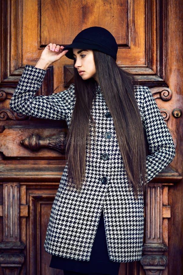 Mooie modieuze donkerbruine vrouw met het lange haar stellen dichtbij houten deur die laag dragen royalty-vrije stock fotografie