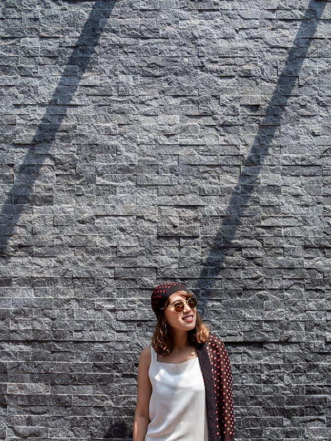 Mooie modieuze hipster Aziatische vrouw op de moderne grijze achtergrond van de bakstenen muurtextuur royalty-vrije stock afbeelding