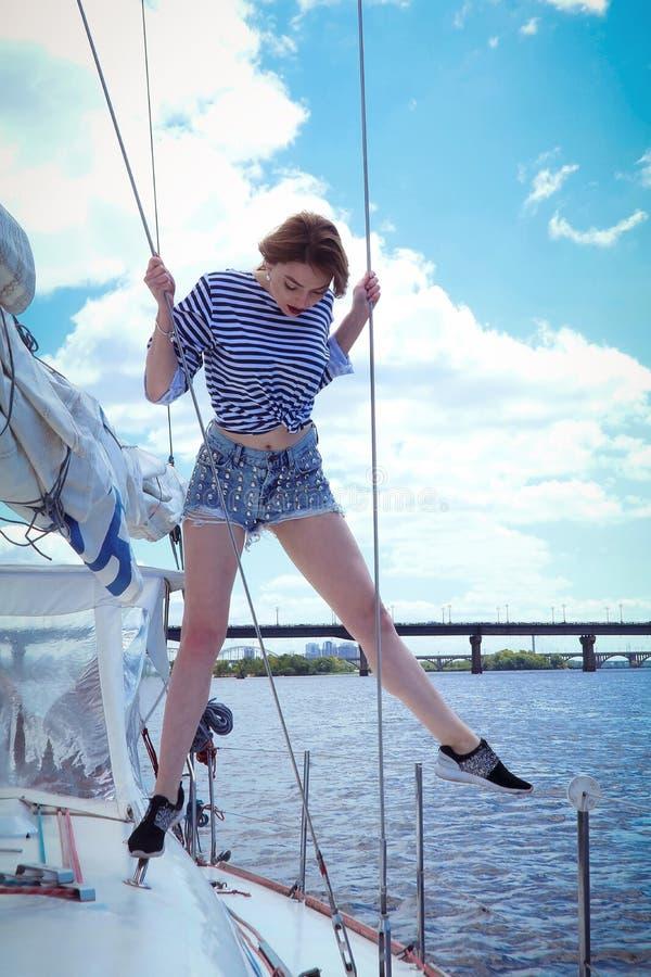 Mooie modieuze jonge vrouw in gestreepte kleren die zich op jacht in zonnige de zomerdag bevinden royalty-vrije stock fotografie
