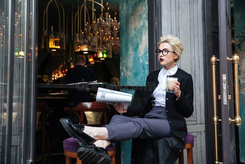Mooie modieuze meisjeszitting in koffie en lezingstijdschrift stock foto's