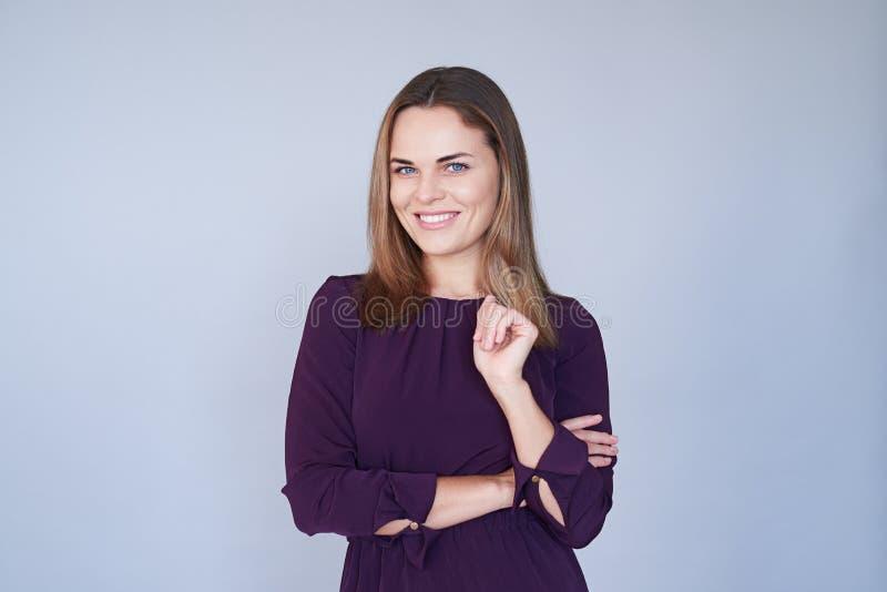 Mooie modieuze moderne vrouw die zich met gevouwen wapens en KMIO bevinden stock foto's