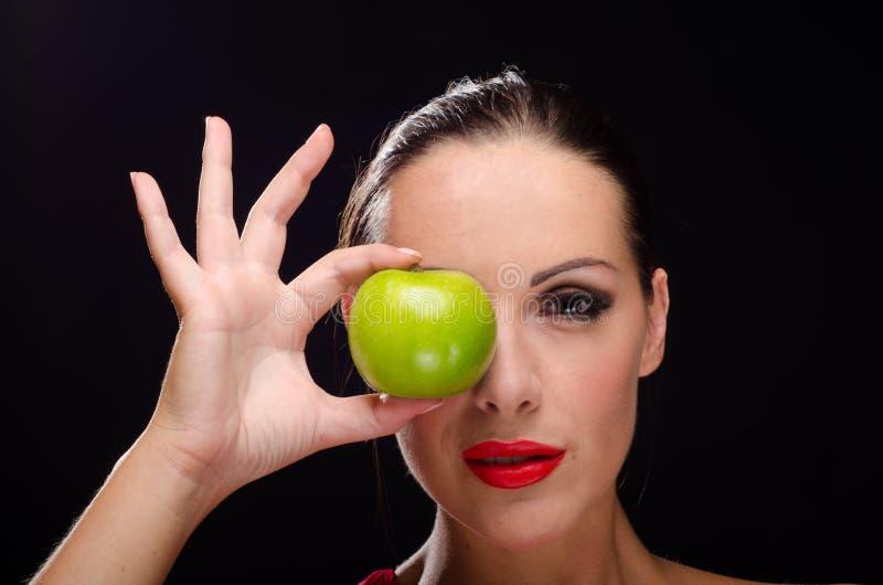 Mooie, modieuze vrouw die een appel eten stock fotografie