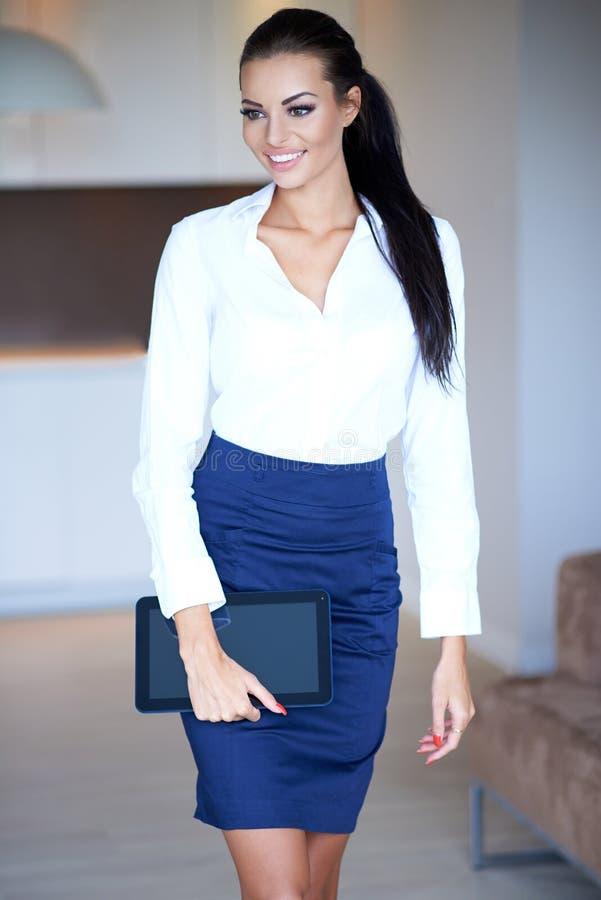 Mooie modieuze vrouw die een tablet dragen stock foto's