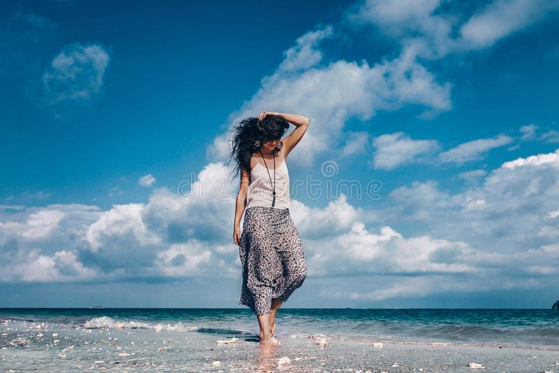 Mooie modieuze vrouw die op het strand lopen royalty-vrije stock foto