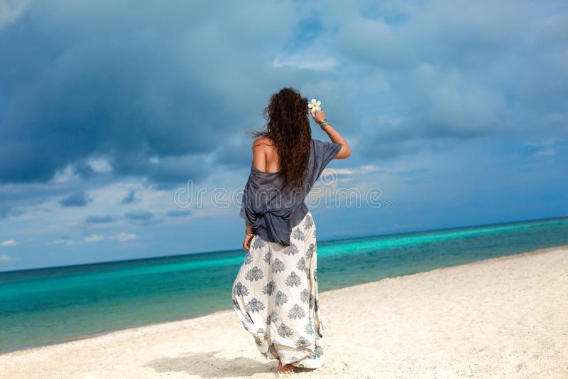 Mooie modieuze vrouw die op het strand met frangipanibloem lopen stock afbeeldingen