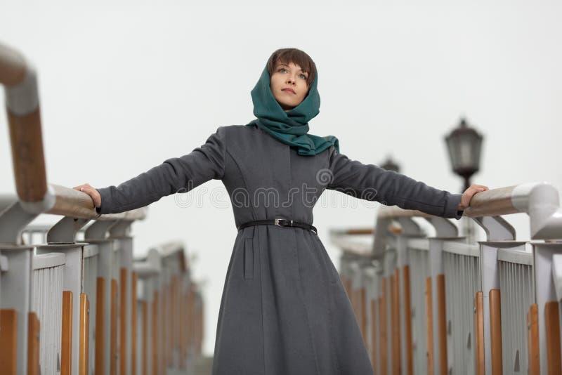 Mooie modieuze vrouw in grijze laag stock foto
