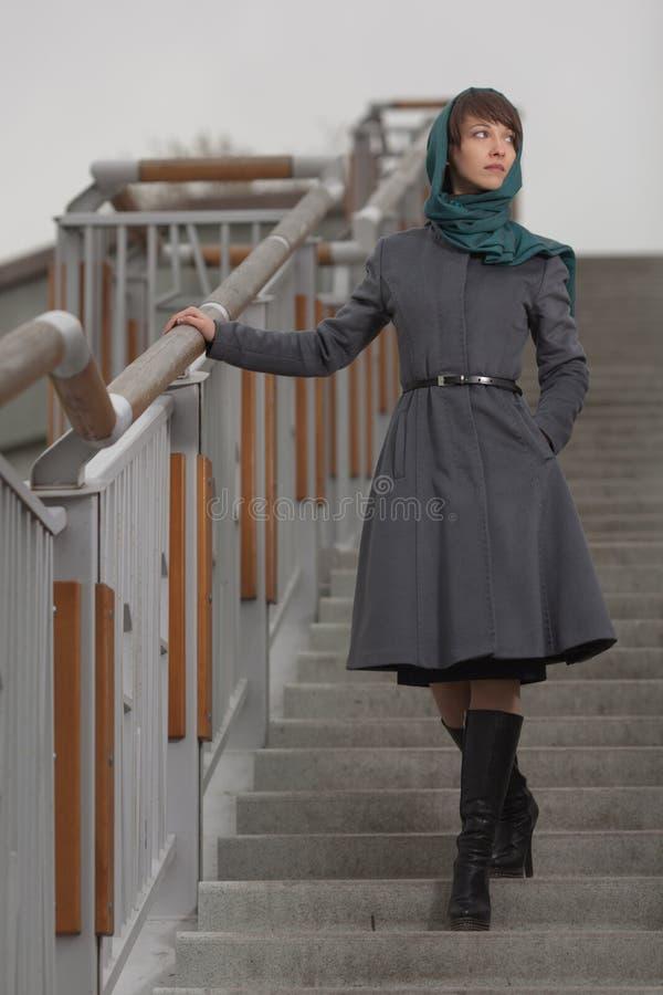 Mooie modieuze vrouw in grijze laag die zich op treden bevinden stock foto