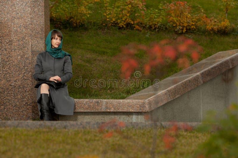 Mooie modieuze vrouw in grijze laag in openlucht stock fotografie