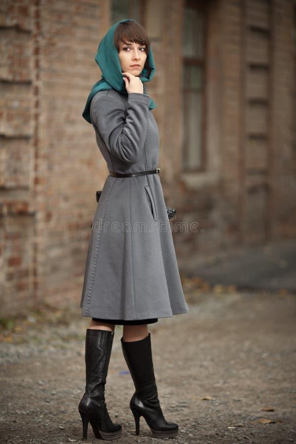 Mooie modieuze vrouw in grijze laag in openlucht royalty-vrije stock afbeelding
