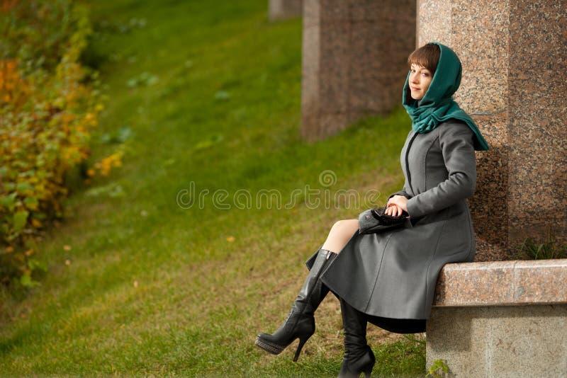 Mooie modieuze vrouw in grijze laagzitting in openlucht stock foto's