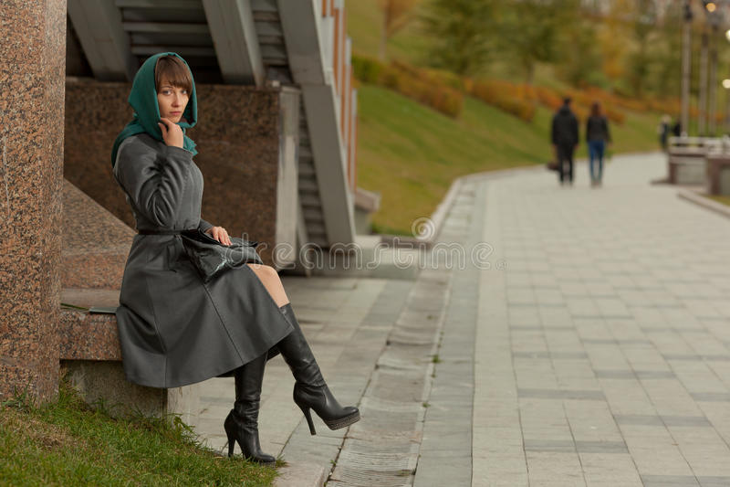 Mooie modieuze vrouw in grijze laagzitting in openlucht royalty-vrije stock foto