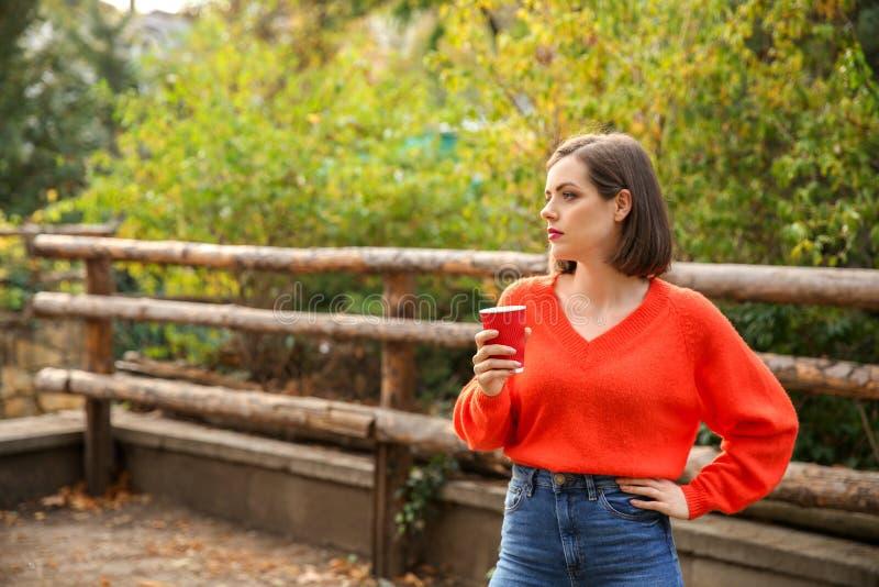 Mooie modieuze vrouw het drinken koffie in de herfstpark stock foto's
