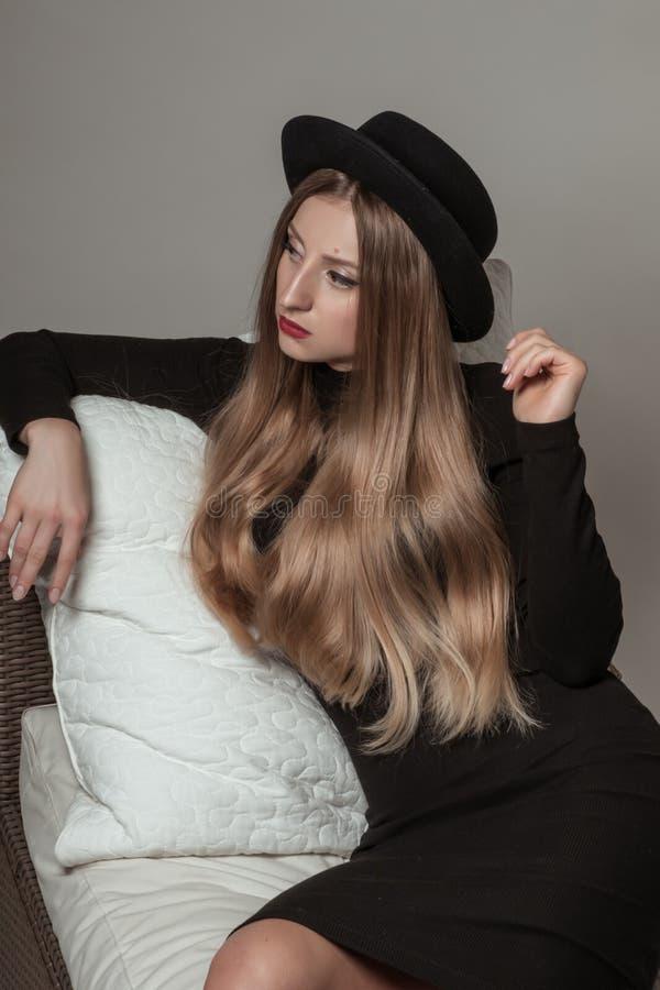 Mooie modieuze vrouw met blonde lang haar in zwarte kleding en hoed royalty-vrije stock afbeelding