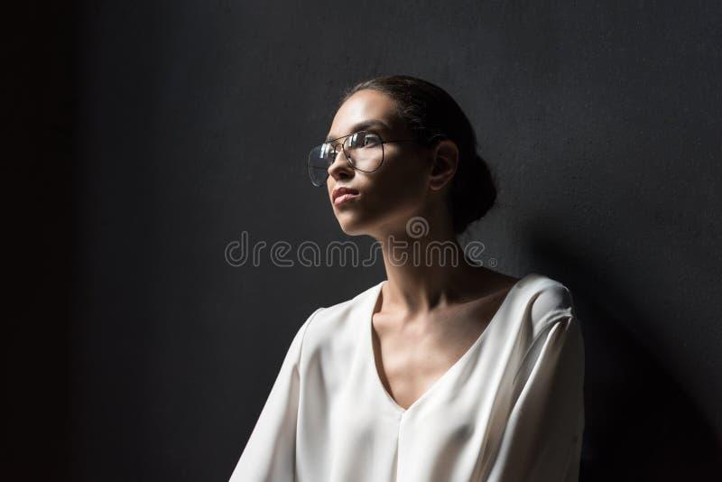 mooie modieuze vrouw in witte blouse en oogglazen die zich in zonlicht bevinden, stock afbeelding