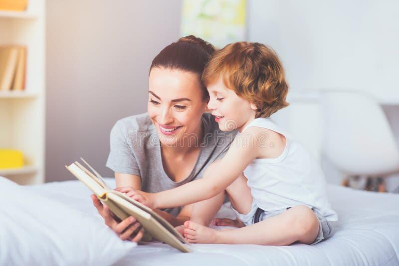 Mooie moeder die een boek lezen aan haar mooie zoon stock foto's