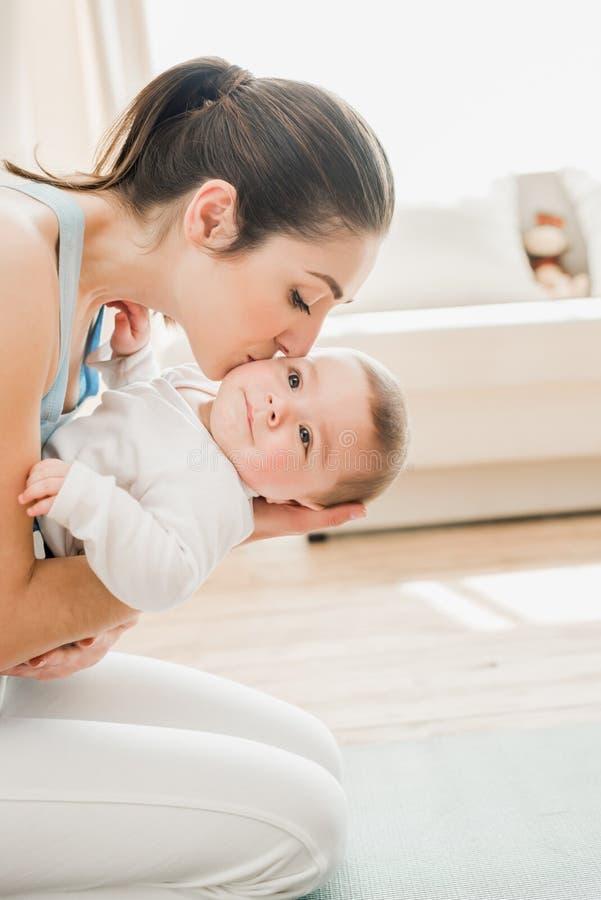 Mooie moeder die en babykind thuis kussen koesteren stock fotografie