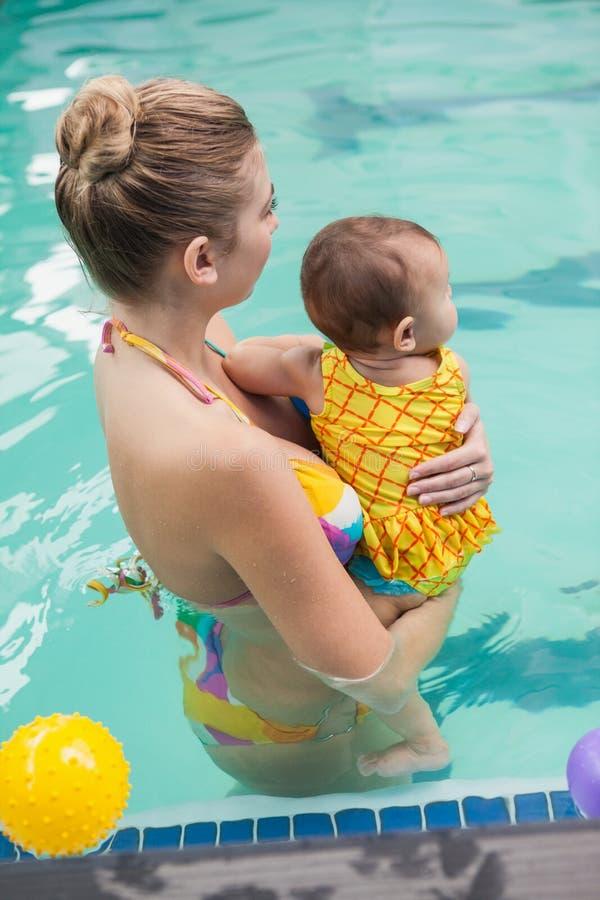 Mooie moeder en baby bij het zwembad stock afbeelding