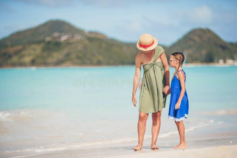 Mooie moeder en dochter die bij Caraïbisch strand de zomer van vakantie genieten royalty-vrije stock afbeeldingen