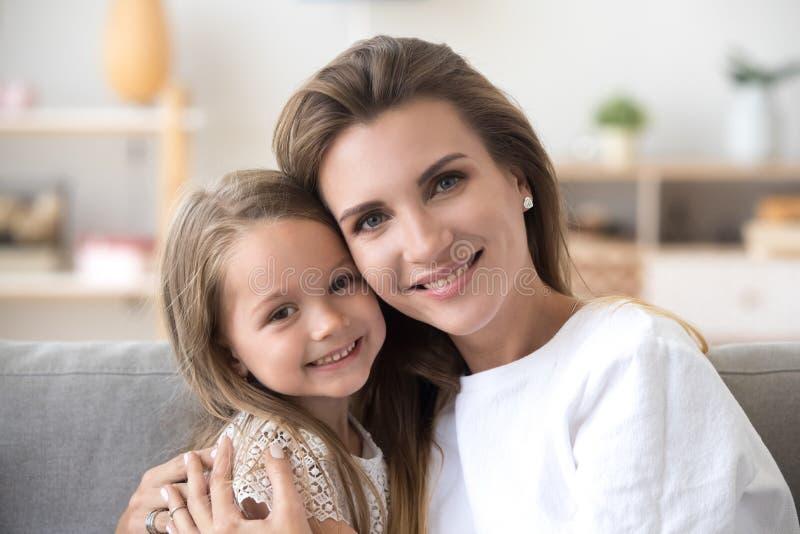 Mooie moeder en dochterzitting op laag die camera bekijken stock afbeeldingen