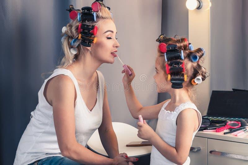 Mooie moeder en haar dochter die pret met lippenstift hebben terwijl doe stock foto