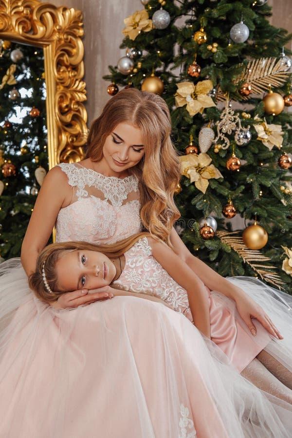 Mooie moeder en haar het leuke dochter stellen dichtbij verfraaide Nieuwjaarboom stock foto