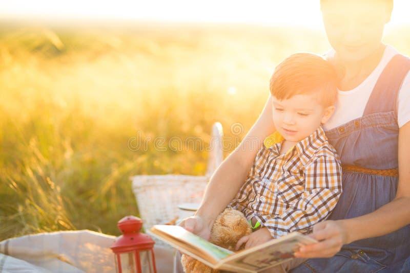 Mooie moeder en haar leuke zoon die een boek op een picknick op de zonsondergangachtergrond lezen Gelukkig familie en onderwijsco royalty-vrije stock fotografie